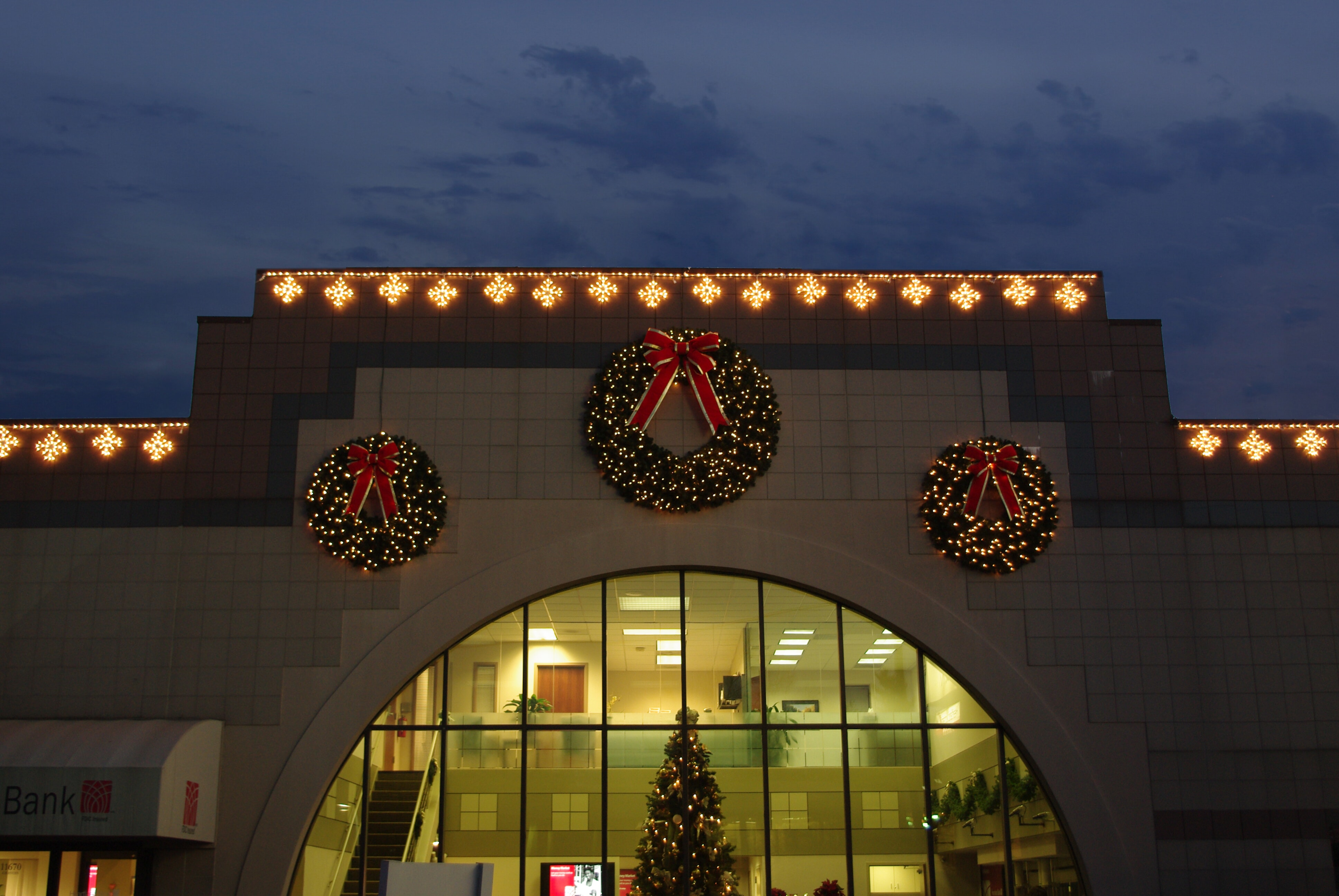 commercial property with holiday wreath and light display