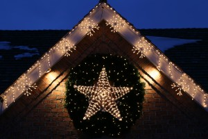 Lit up star and wreath outside a house