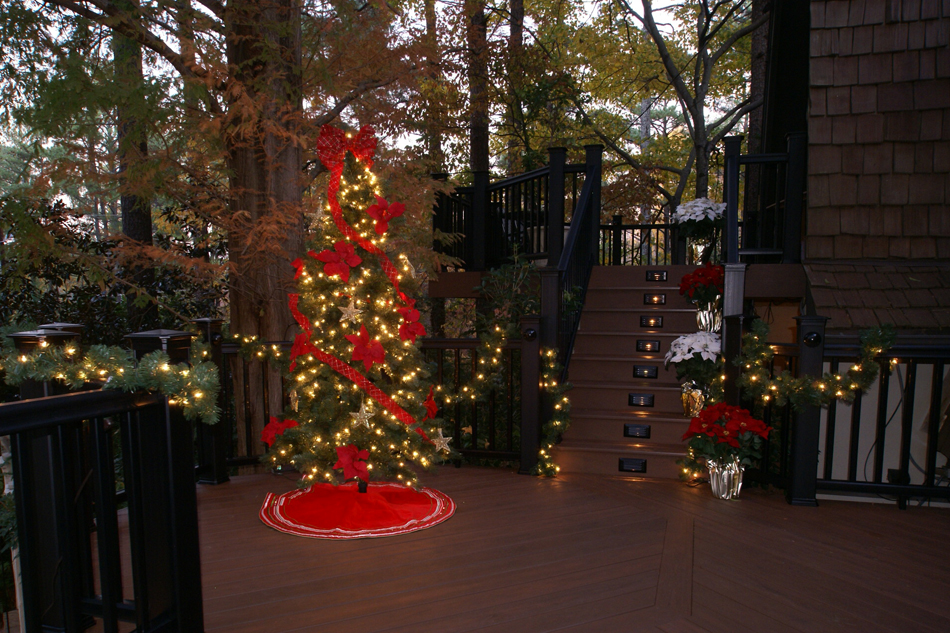 Christmas tree on a deck outside of a home
