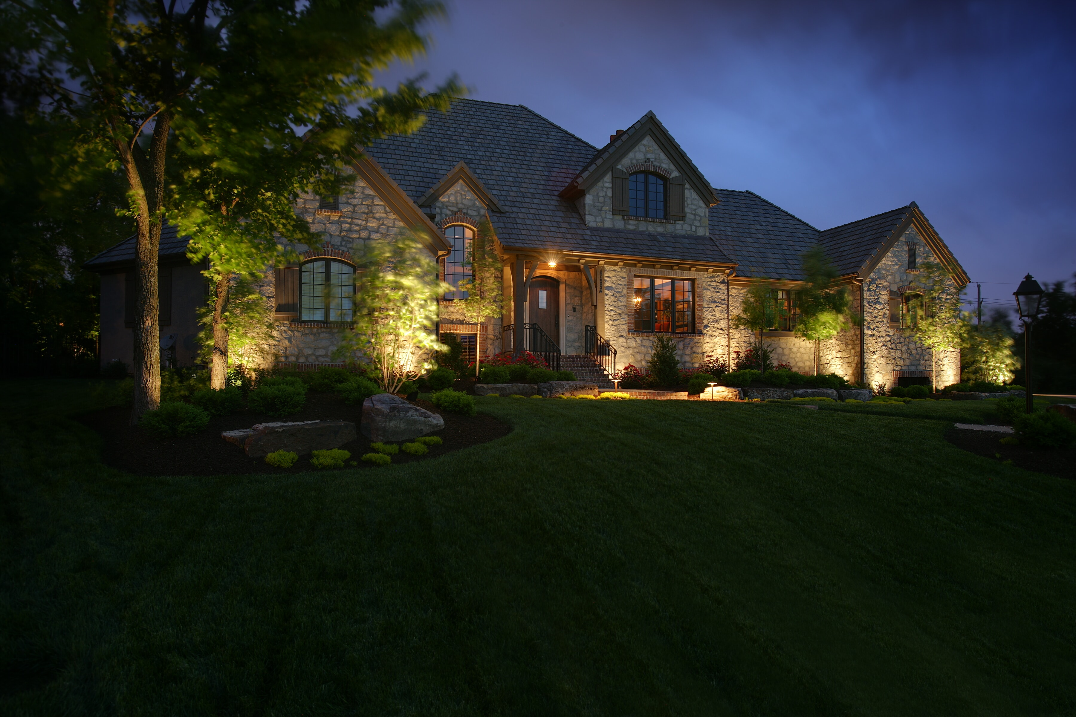 House with Green Lawn and Up Lighting Accents