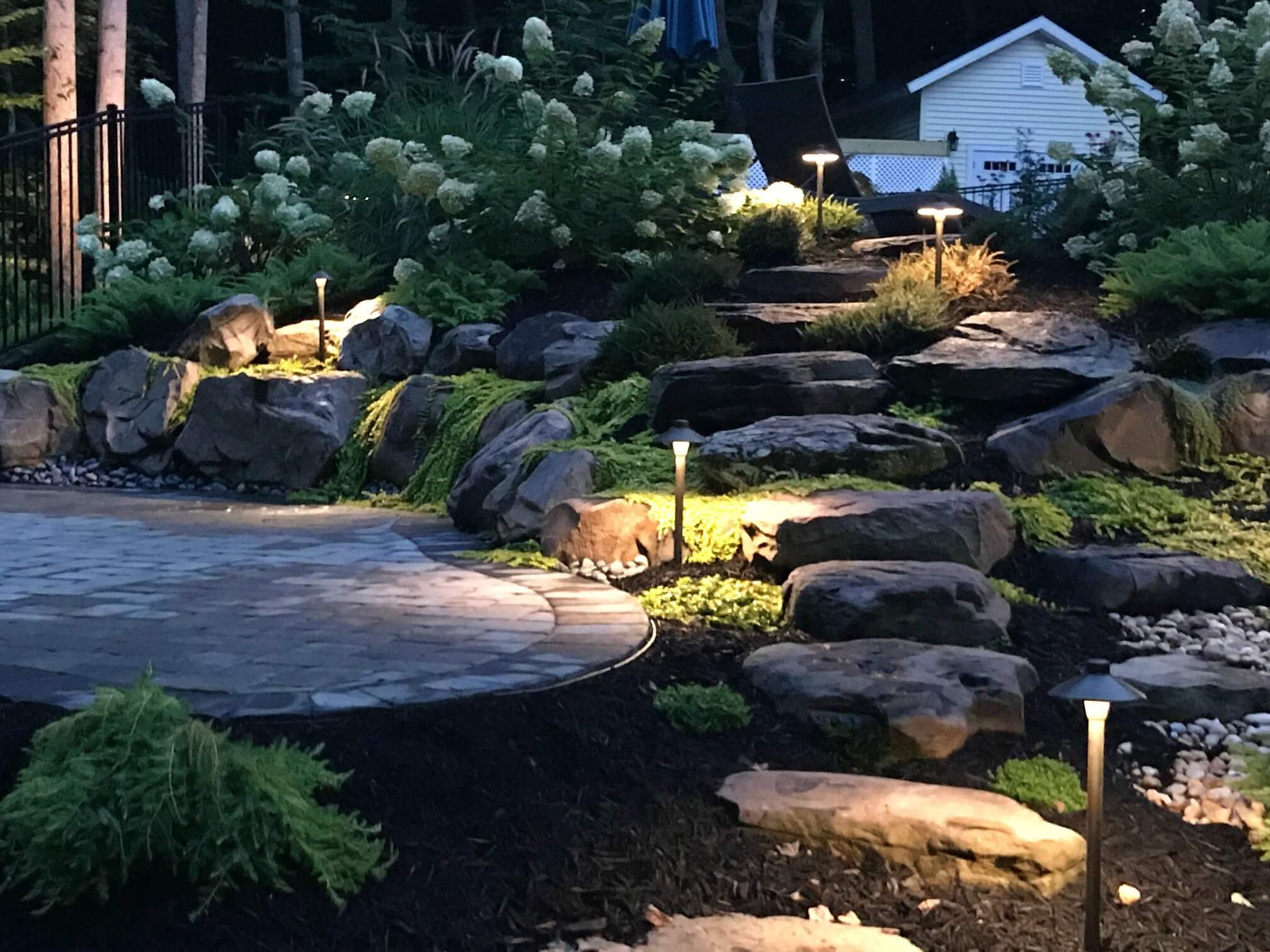 Lit landscaping and rock steps