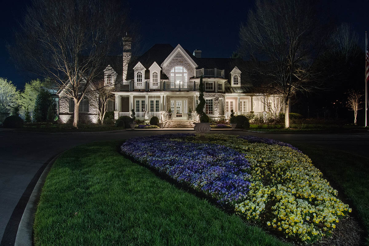 Well lit house and flowerbed