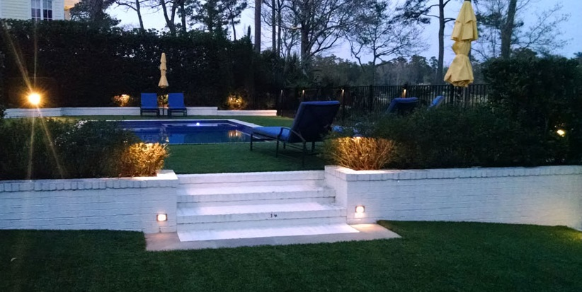 upscale backyard with pool and outdoor lights