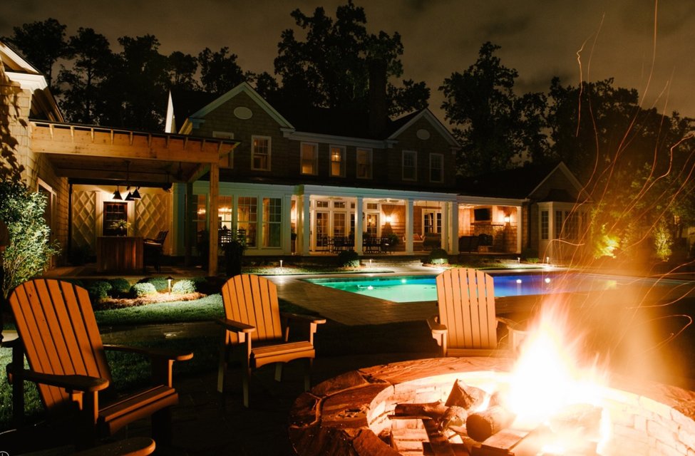 backyard with pool and fire pit lighting