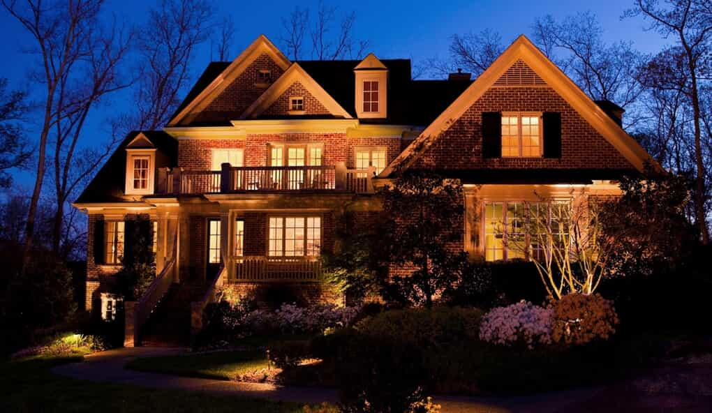 large home with illuminating lights on the house