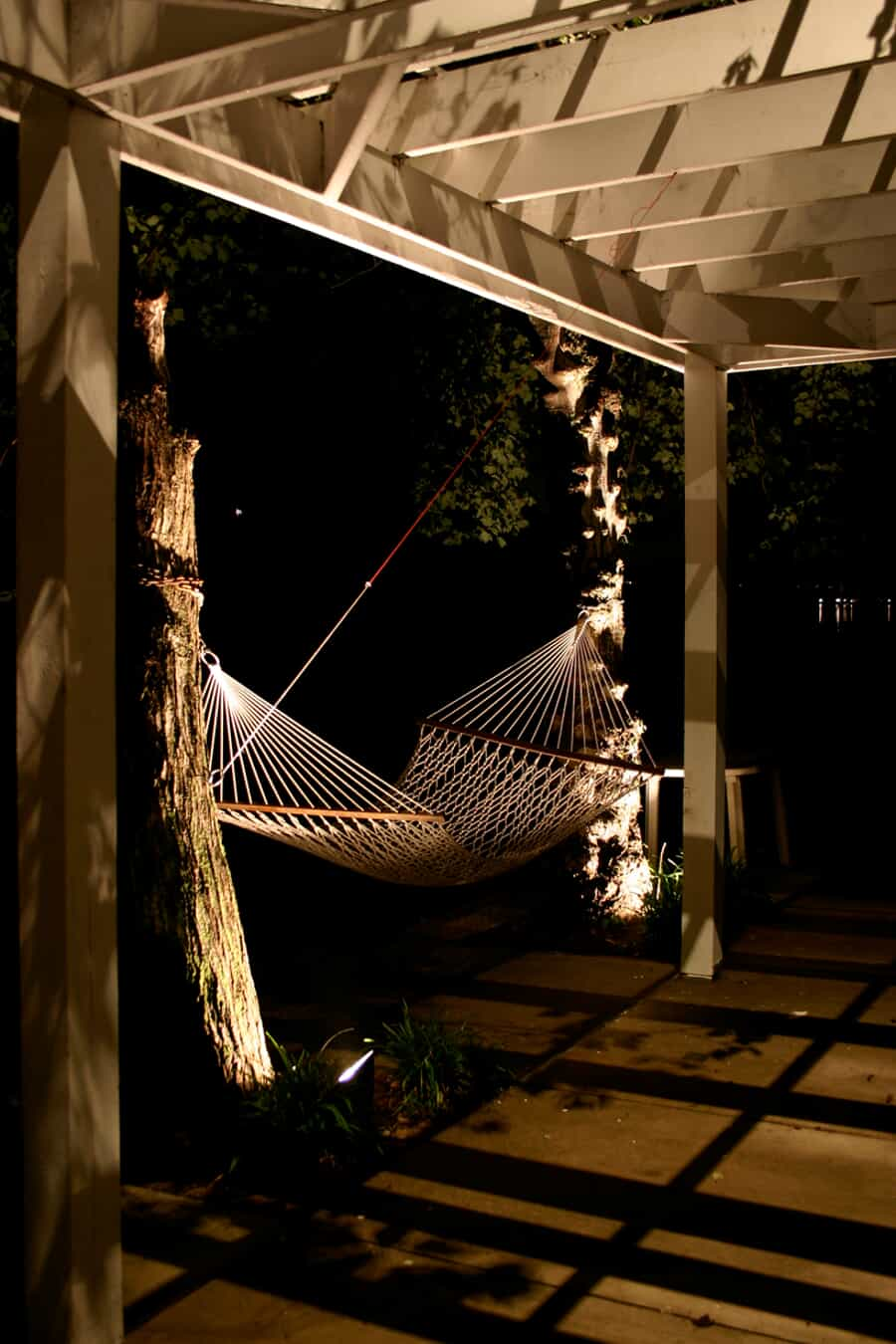 a backyard hammock next to trees that have halogen lights illuminating them