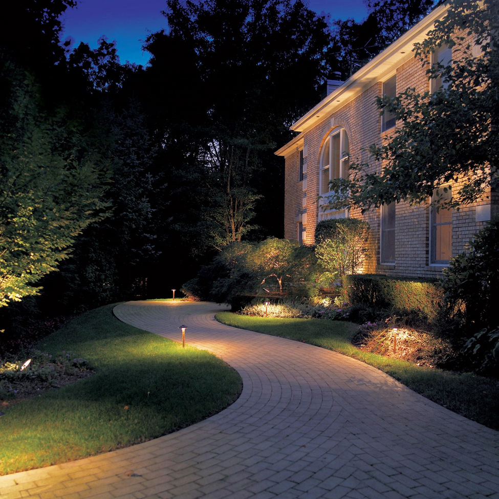 path a long the side of a brick house lit by OLP lighting