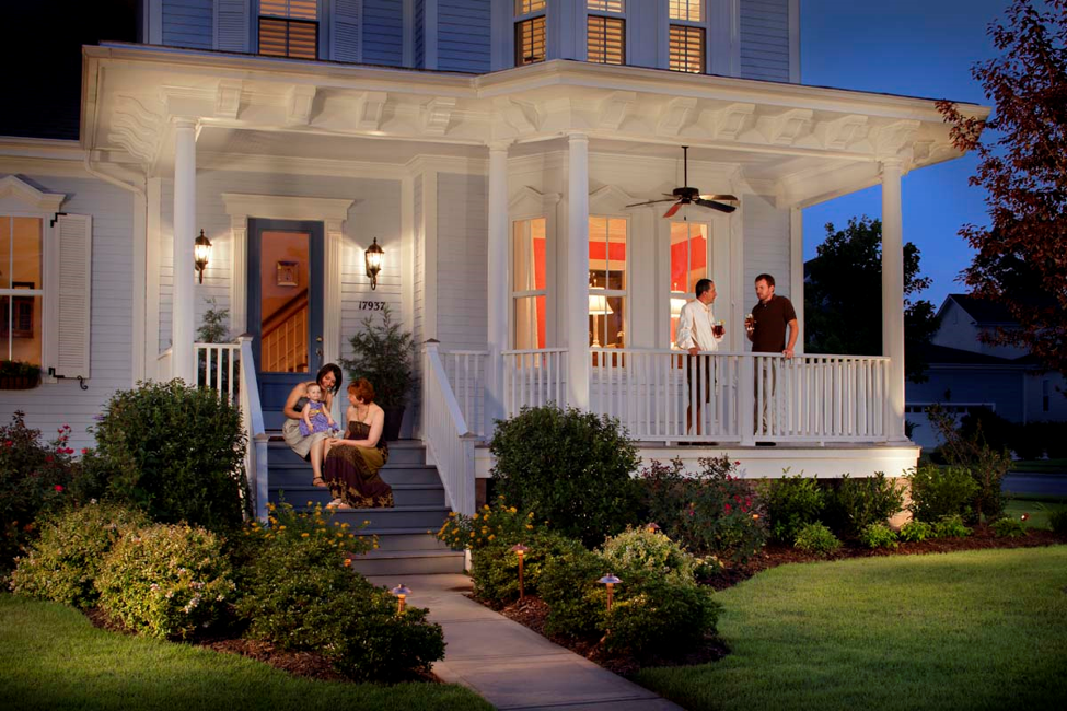 front porch lighting of a white house with people sitting on the porch