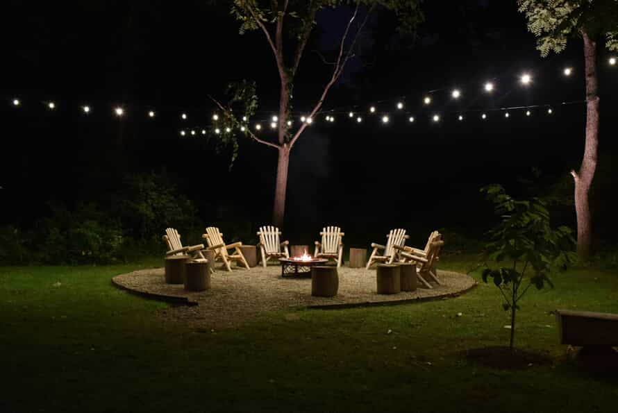 Outdoor area with fireplace and string lighting