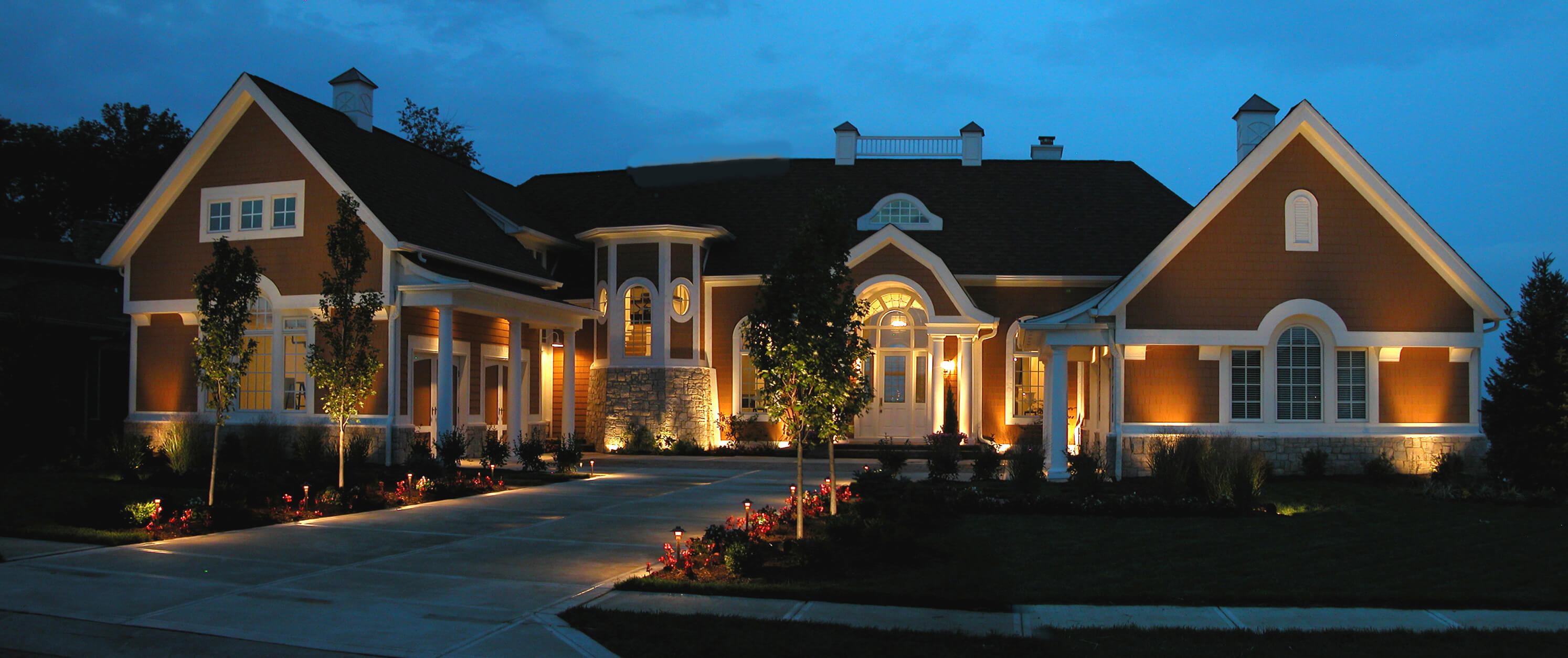 Red and white building and driveway that has specialty lighting