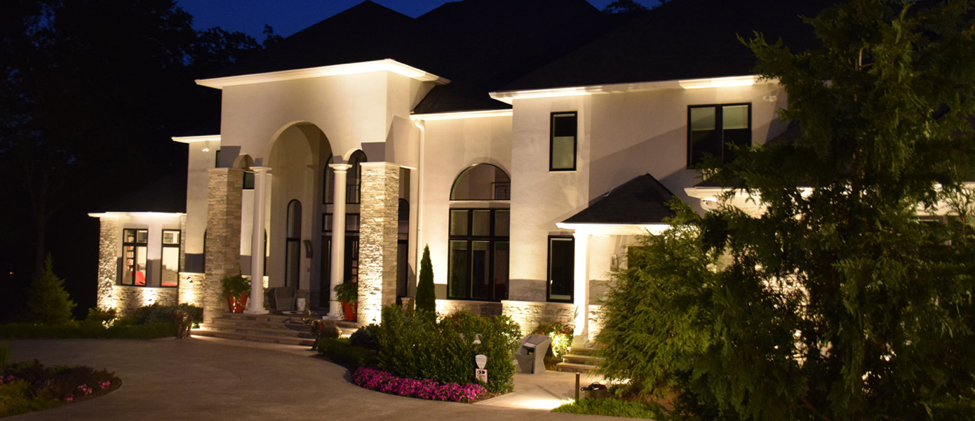 a white home with illumination lighting on the driveway and front porch