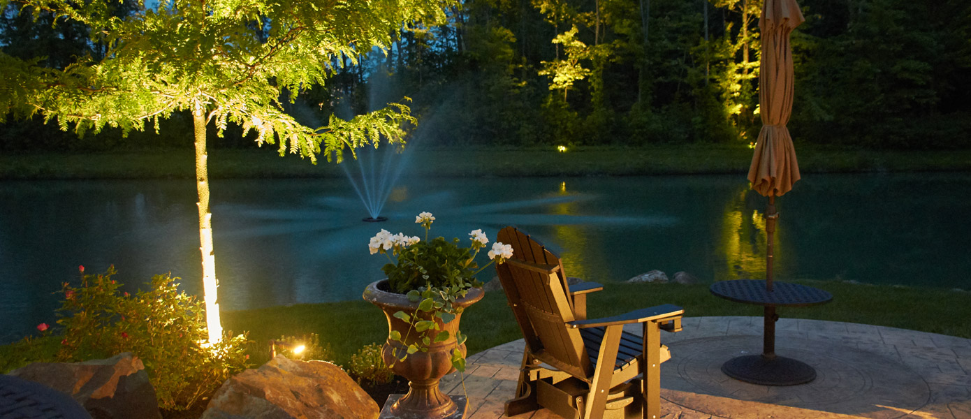 outdoor seating area in front of pond with lit trees