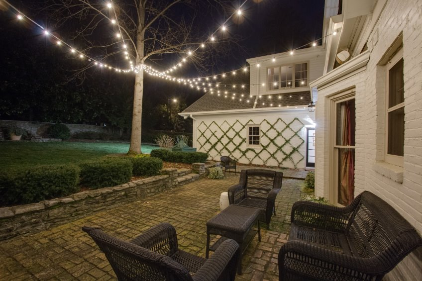 patio seating area lit by string lighting attached to tree and house