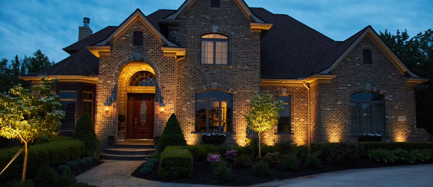 architectural lighting of a brick house and surrounding plants
