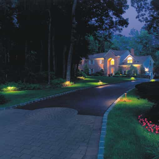 Driveway and home with beautiful outdoor lighting