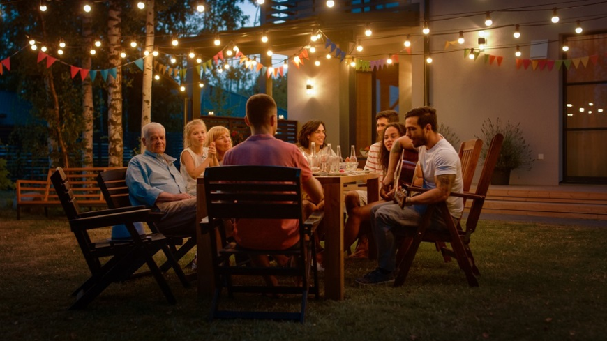 group of people around a table at outdoor patio with string lighting