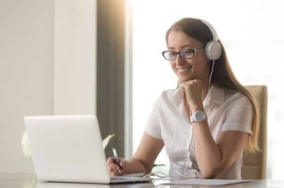 Woman on laptop at home with headphones on taking notes