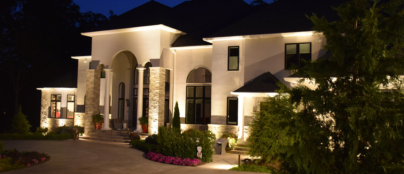 architectural lighting on the front of a white house with stone accents and trees
