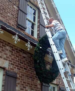 Man on a ladder putting up Christmas lights