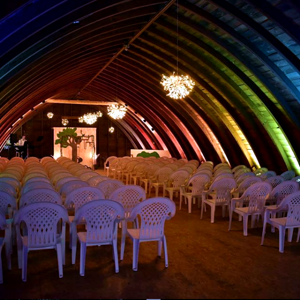 barn with rainbow wedding lighting