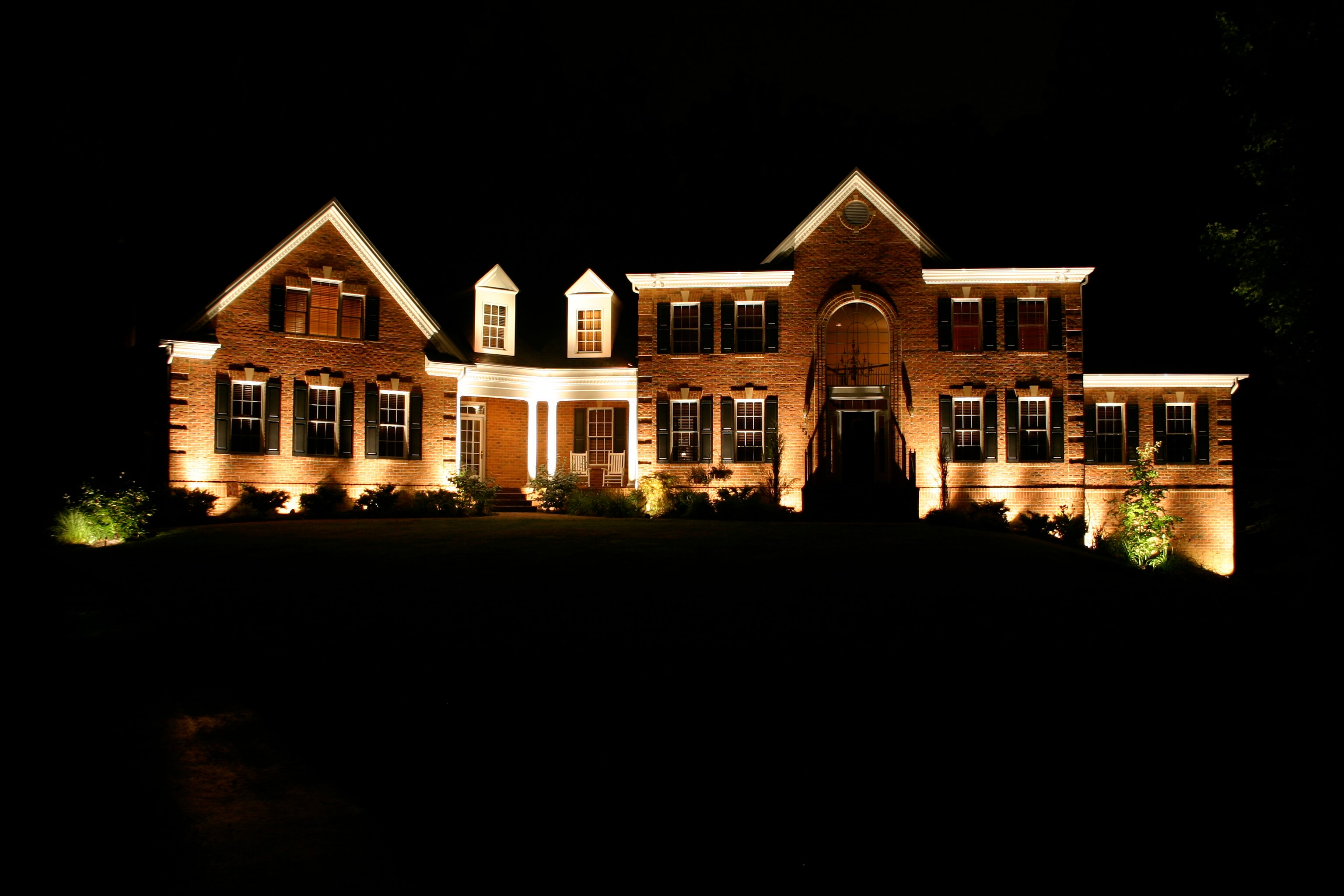 Wide shot of a home with beautiful outdoor lighting