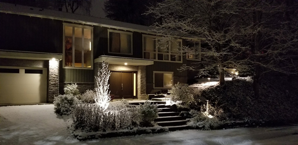 The front of a home, covered in snow at nighttime