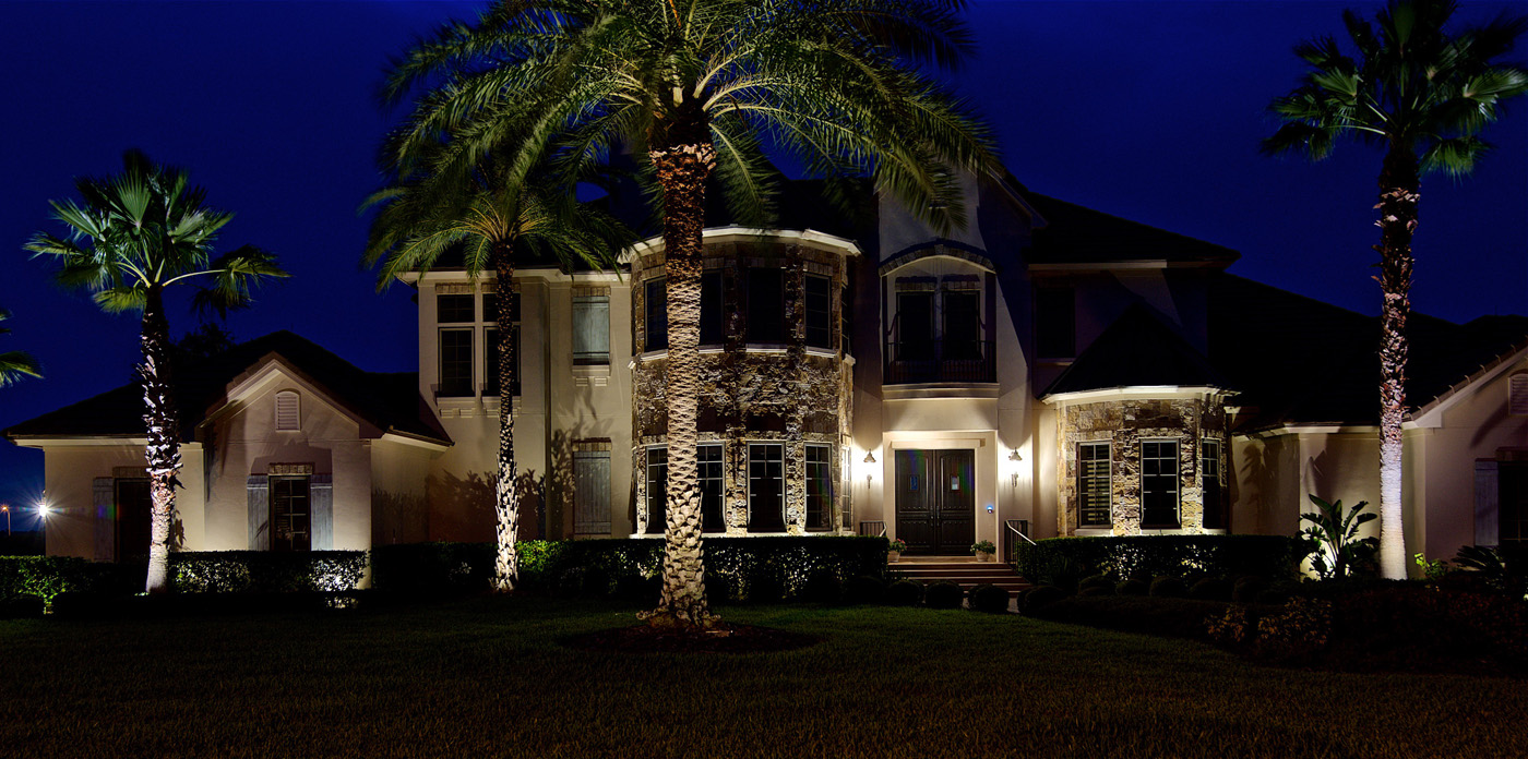 front of a house lit by architectural lighting and palm trees lit