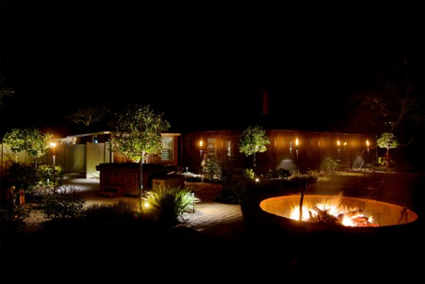 backyard with outdoor lighting, trees, and a fire pit
