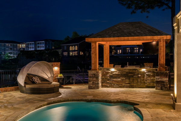 pool, chairs, and outdoor bar lit with OLP lighting