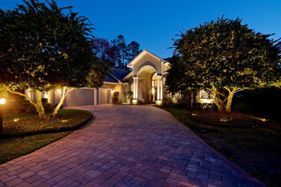 exterior lighting of a house and drive way as well as landscape lighting on trees