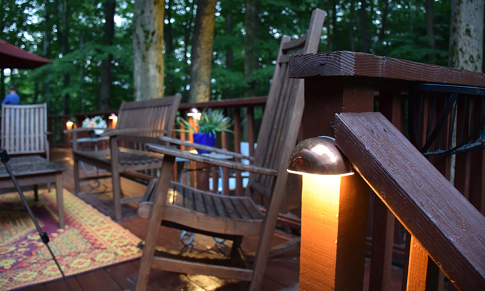 Deck decorated with chairs, plants, a rug and outdoor lighting