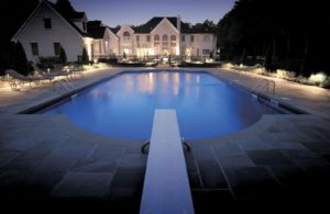 beautiful pool with outdoor lighting