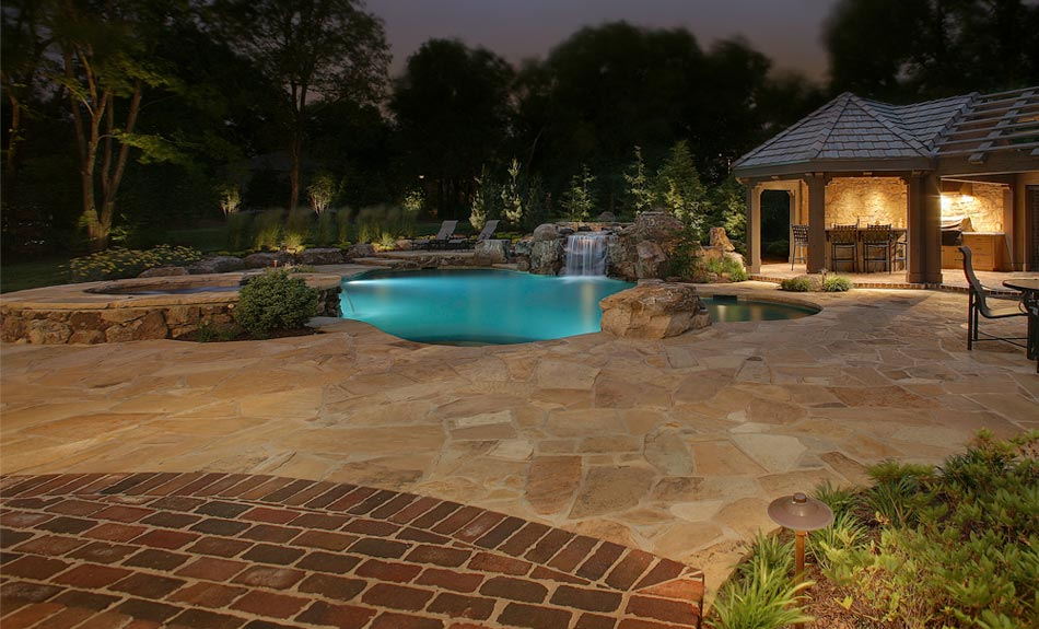 Outdoor pool and deck with with a lounge area and special lighting