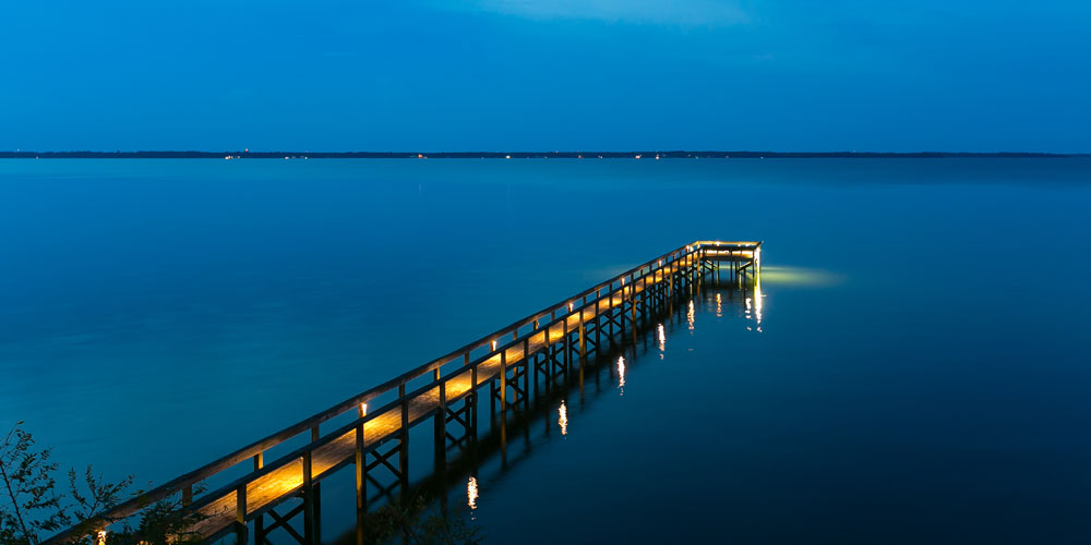 Beautifully lit dock leading out to a lake