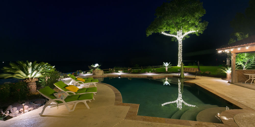 Pool and deck with lounge chairs, all lit by special lighting
